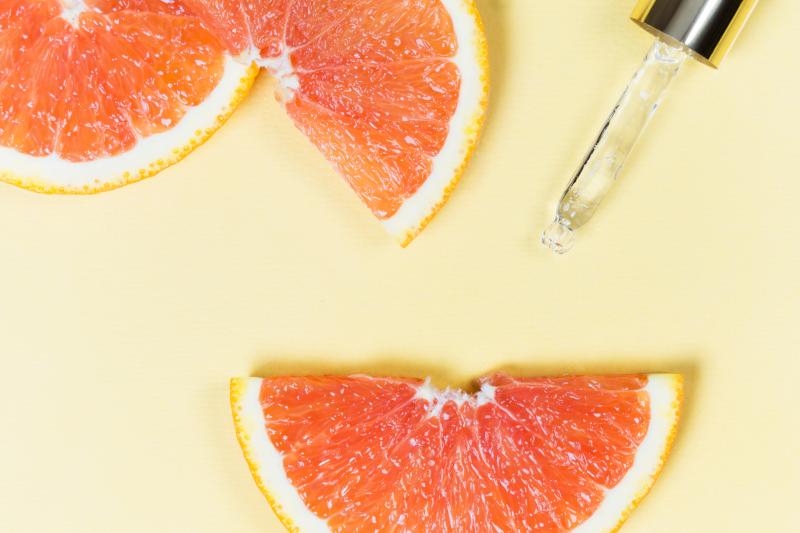 Cosmetic Solutions Trends Report Webinar Image features a dropper on a yellow background among slices of citrus skin care ingredients