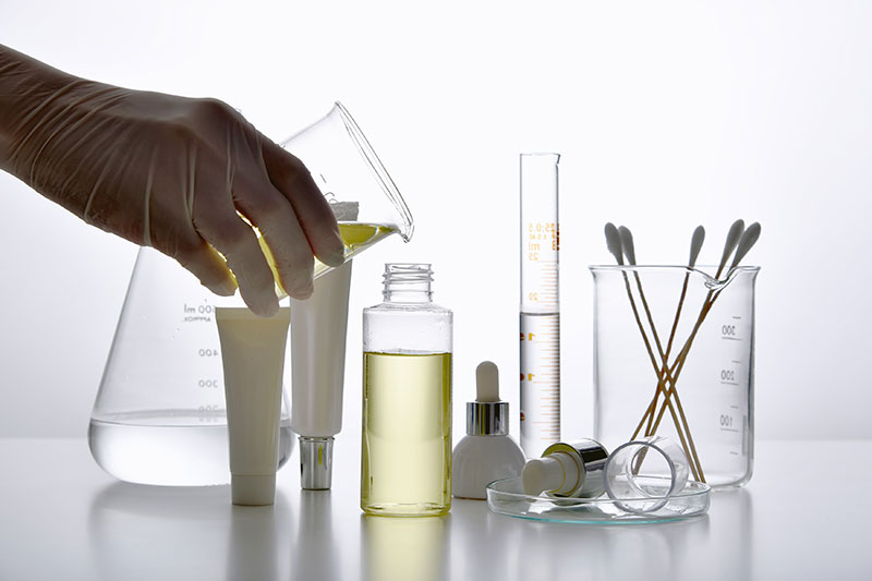 Regulatory Compliance Image shows various skin care bottles and products in a laboratory environment