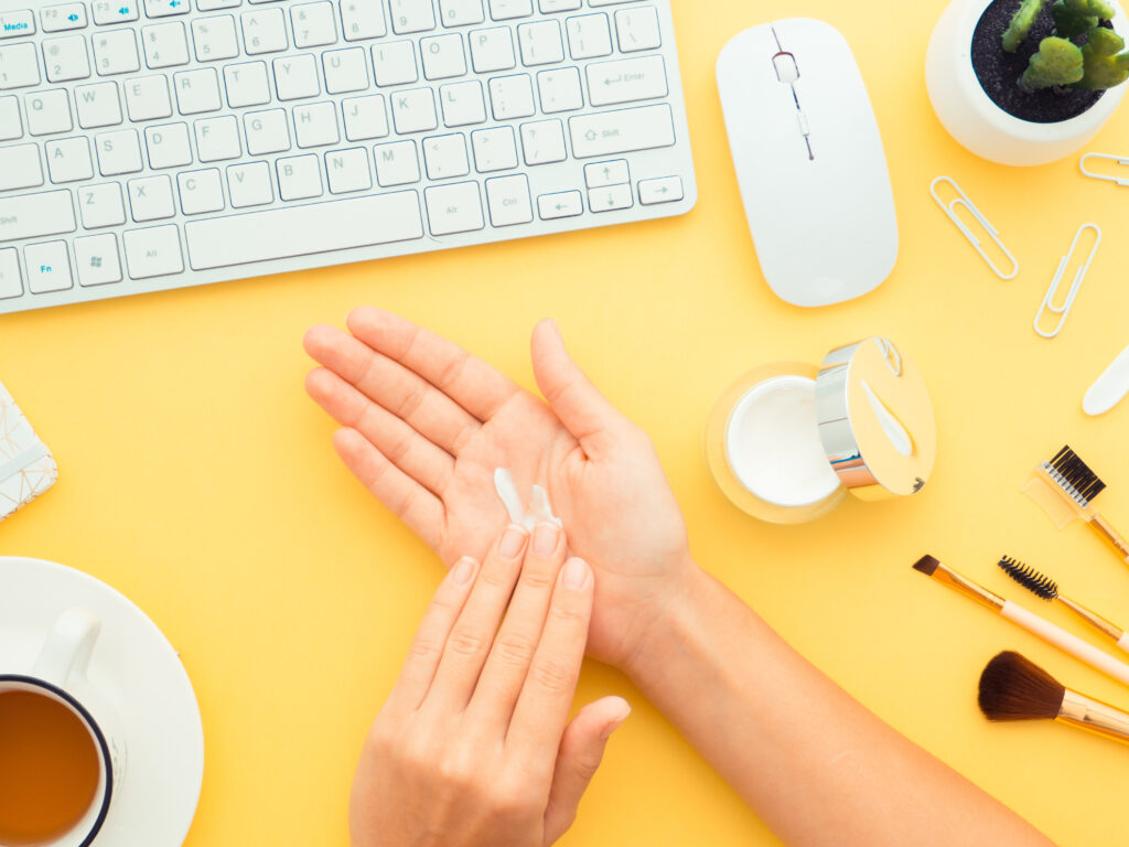 Cosmetic Solutions Account Management Image features a models hands near a computer mouse and keyboard. The model is applying private label skincare cream into her hands.