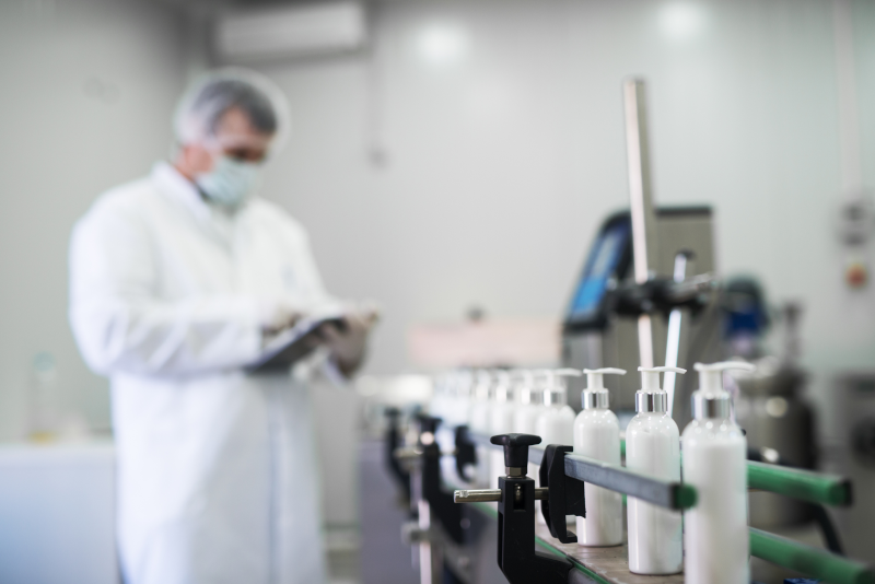 Cosmetic Solutions Quality Assurance image features a quality control officer inspecting skincare bottles on a manufacturing line