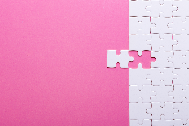 Private Label Skincare manufacturers Cosmetic Solutions White Space Mapping Image features a White puzzle piece being slotted into a blank white puzzle. The puzzle sits on a pink background
